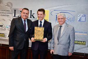 Milton Sperafico recebe o troféu Moura Brito das mãos do jornalista Alexandrino Bispo Neto e do desportista Celso Pavia